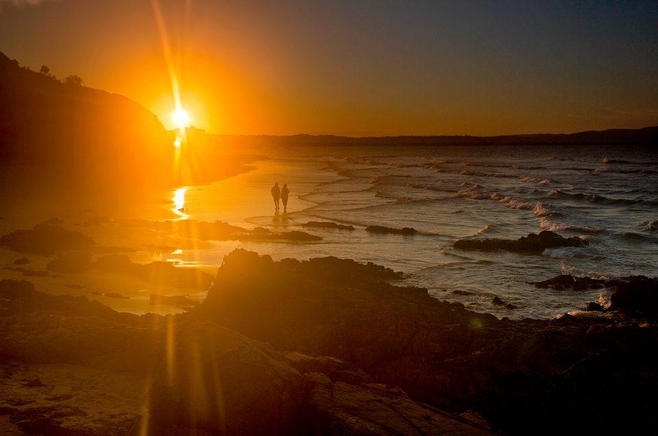 A couple romatically walk along the beach at sunset at Byron Bay